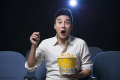 Stock Photo of Young man watching horrible movie in cinema