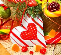 christmas pine twigs, heart, christmas balls with pine cones, sweets and jell - stock photo