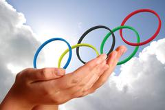 Olympic rings  in young womans hands against the sky Piirros