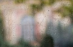 Raindrops on window with colorful background Stock Photos