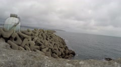 4K View of white reservoir at edge of sea in front of manmade rocks Stock Footage