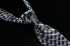 Stock Photo of grey or gray windsor knot on tie isolated against black