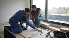 carpenter with trainees installing wooden floor - stock footage