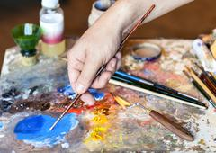 Hand of the artist with a paintbrush and artistic equipment: paint, brushes,  Stock Photos