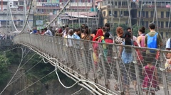 People crossing Laxman Jhula footbridge on river Ganga, Rishikesh, India Stock Footage