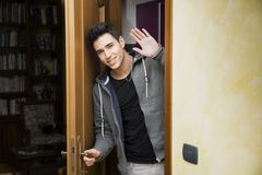 Smiling young man getting out of door waving at the camera - stock photo