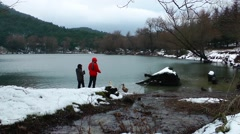Children Feeding the Goose near the Lake in Winter Stock Footage
