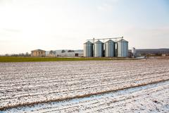acres with snow in winter with silo in beautiful light and structure - stock photo