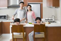 Happy young family cooking in kitchen Stock Photos