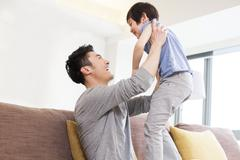 Stock Photo of Father holding son aloft in living room