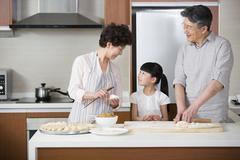 Happy grandparents and granddaughter making dumplings Stock Photos