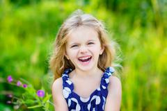 Fanny and beautiful laughing little girl with long blond curly hair, outdoor Stock Photos