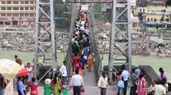 People crossing Laxman Jhula footbridge on river Ganges, Rishikesh, India Stock Footage