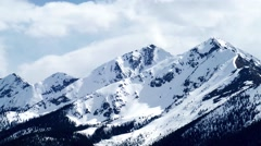 Zoom in on snow capped Rocky Mountain peaks - stock footage