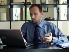 Stock Video Footage of Businessman comparing data on smartphone and laptop in the office NTSC