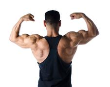 back double bicep pose of male bodybuilder - stock photo