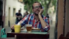 Portrait of happy young man sitting in outdoor bar HD Stock Footage