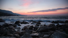 Waves break about stones at sunrise over the sea Stock Footage