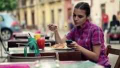 Young woman with smartphone eating salad in outdoor bar HD Stock Footage