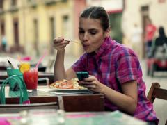 Young woman with smartphone eating salad in outdoor bar NTSC Stock Footage