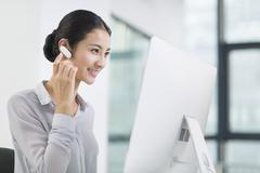 Young businesswoman with Bluetooth headset working in office - stock photo