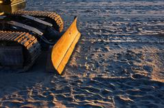 Bulldozer on beach with sunset light Stock Photos
