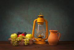 Old lantern and fruits Stock Photos
