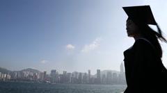 Silhouette happy Asian woman,Graduation cap in waterfront, hong kong skyline-Dan Stock Footage