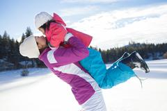 Mother holding daughter aloft on snow ground Stock Photos