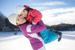 Stock Photo of Mother holding daughter aloft on snow ground