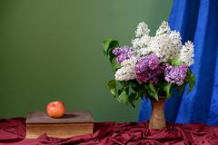 Violet and white lilacs in a vase of of ceramics on the table Stock Photos