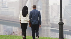 A couple walks hand in hand through the Brooklyn Bridge park after a rain Stock Footage