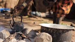 Stock Video Footage of African women boiling water in kettle on bonfire