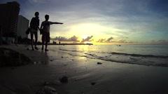Vistors walking beach shores during sunset Stock Footage
