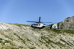 chopper of guardia civil patrulling over the mountain in spain - stock photo