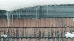 Icicles 002 on rooftop with snow and falling snow in vienna Stock Footage