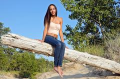 Attractive young woman on log Stock Photos