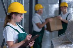 Female manufacturing labourer holding clipboard Kuvituskuvat