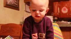 Toddler leans on table looking down Stock Footage