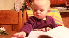 Toddler tries to turn book page Stock Footage
