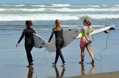 surfing in muriwai beach - new zealand - stock photo