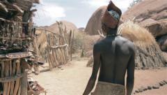 Native damara in namibia walking through his village Stock Footage
