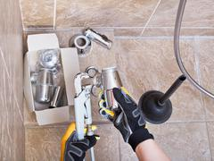 plumber repairs sink trap in bathroom - stock photo