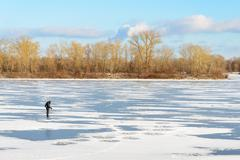 fisherman on the frozen river - stock photo