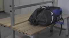 Man unzips his gym bag in the locker room 2 Stock Footage