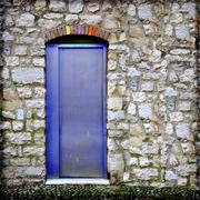 Aluminium door in medieval wall. Coexistence of old and new. Stock Photos