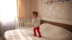 Little baby girl having fun and joy jumping on the bed Stock Footage