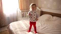 Little kid girl pretending to be asleep - standing on the bed Stock Footage