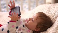 Child watches cartoon on your mobile smartphone lying in bed Stock Footage