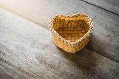 a heart-shaped rattan basket on wooden table - stock photo